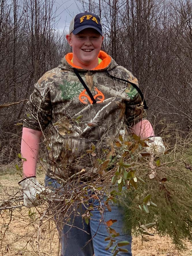 Man holding twigs and brush smiling
