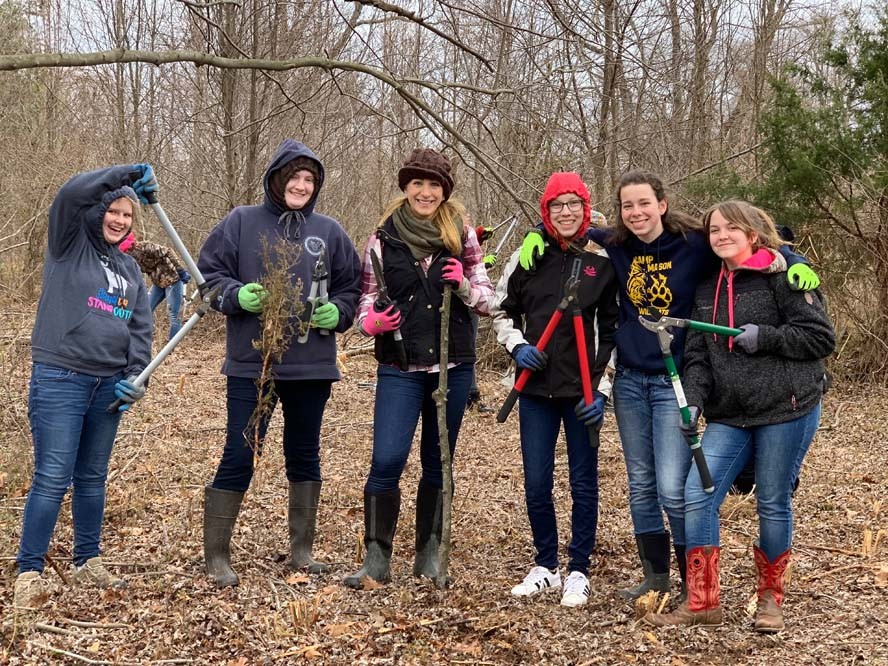 Group-shot of women in woods holding sticks and branch cutters