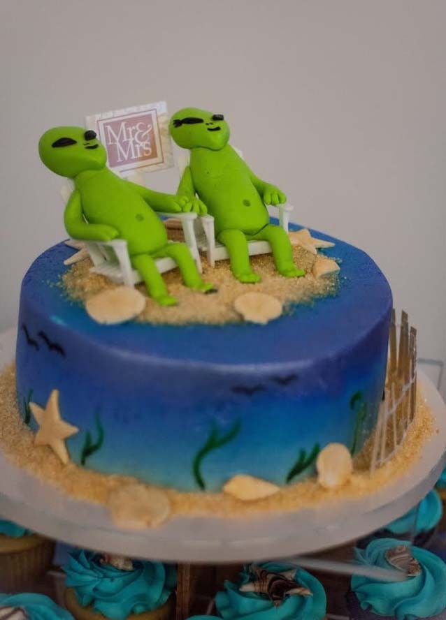 Wedding cake with two aliens sitting in chairs on a beach