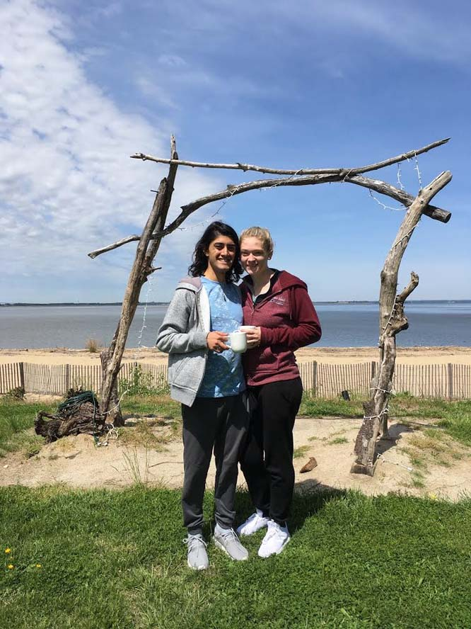 Couple standing under manor outside on beach and grass
