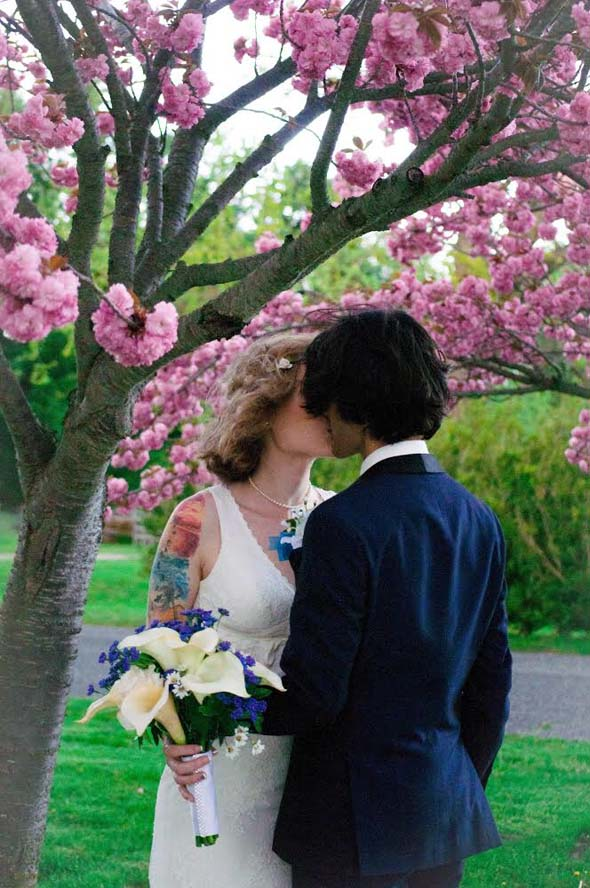 Bride and groom kissing under tree with pink flowers