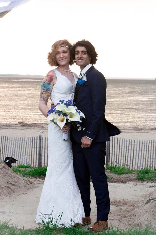 Bride and groom posing for picture on beach