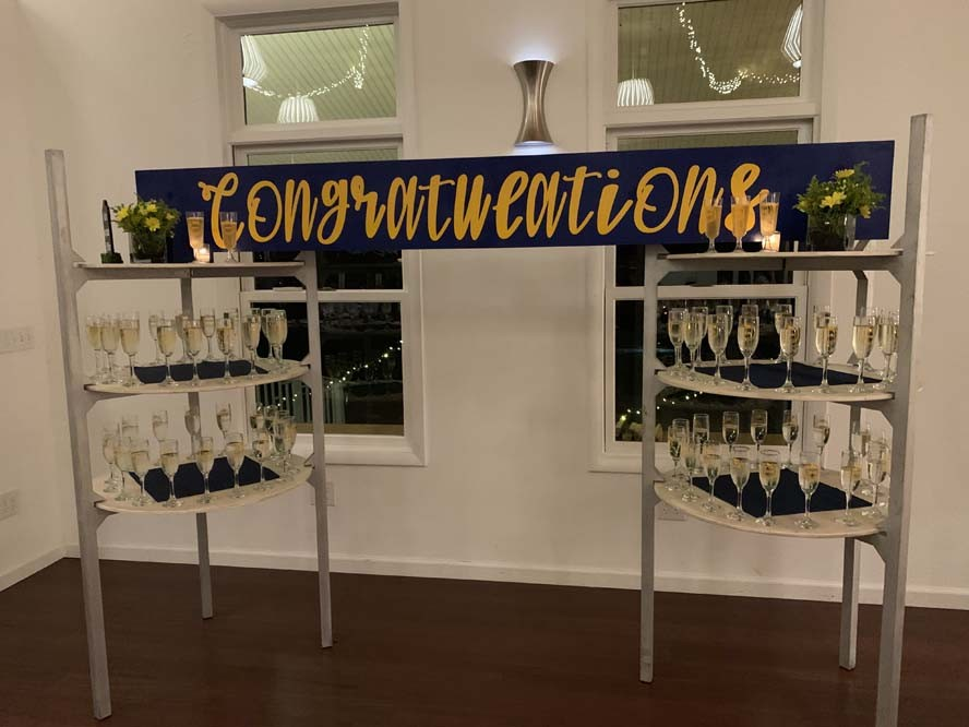 Congratulations sign hanging up with glasses of champagne on shelves