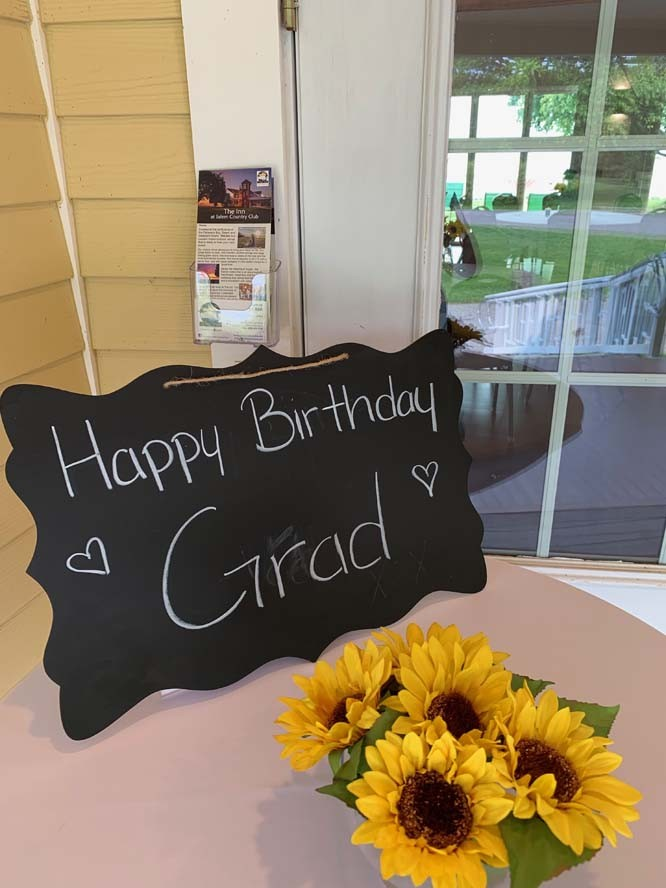 Happy birthday Grad written on chalk board sign with sunflowers on table