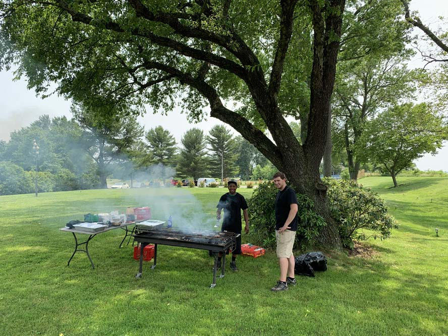 Two men grilling on large grill outside under big tree