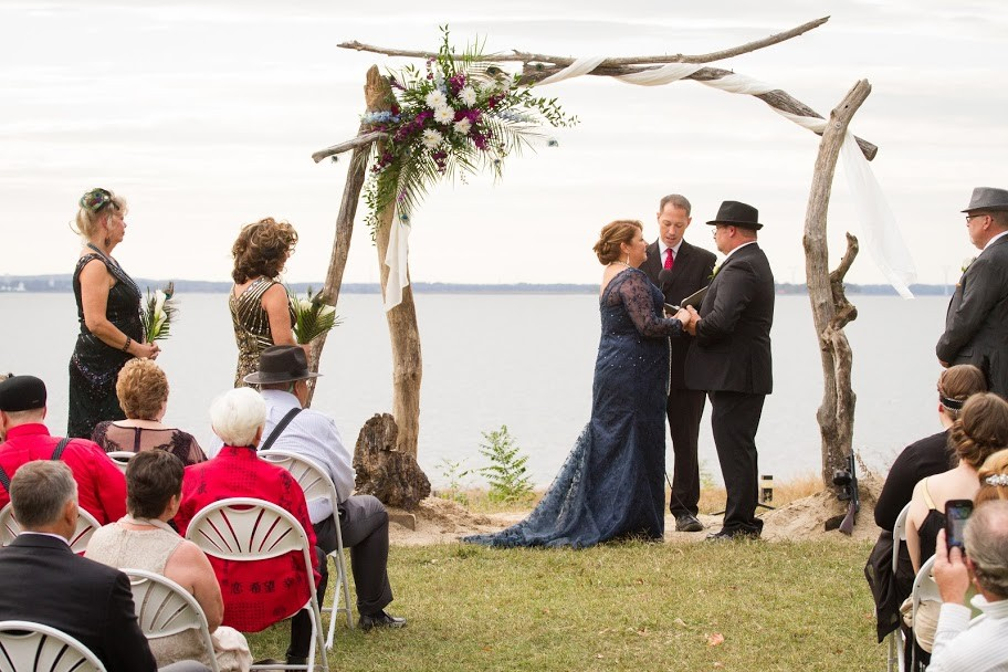 Outdoor wedding with manor infront of body of water