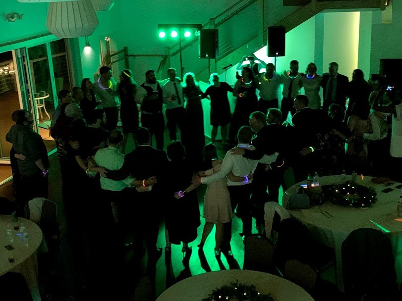 Green glowing lights in reception room, people linked arms in circle