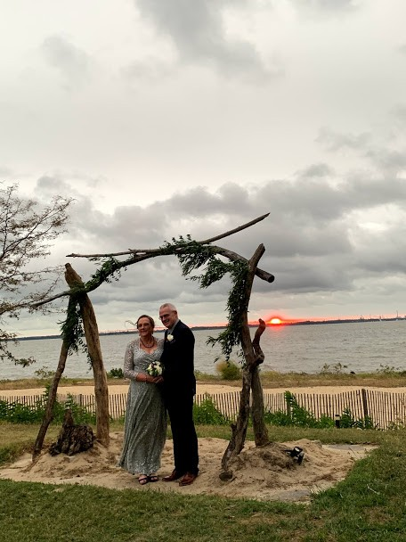 Bride and groom standing under manor on sand with sun setting