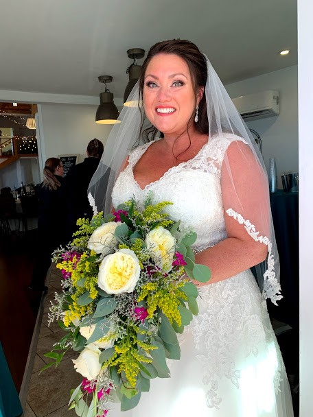 Bride smiling holding bouqet of flowers