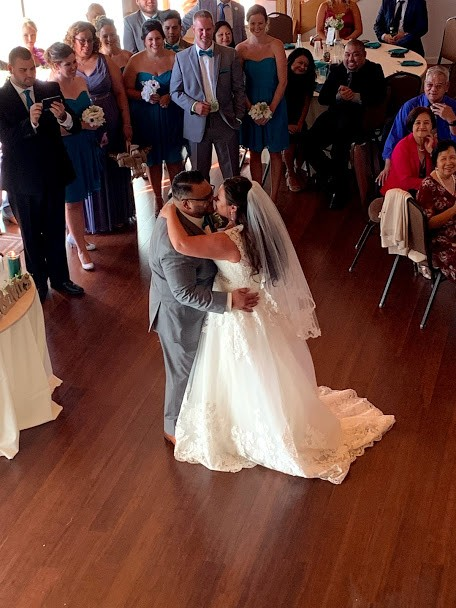 Bride and groom slow dancing in center of wedding reception