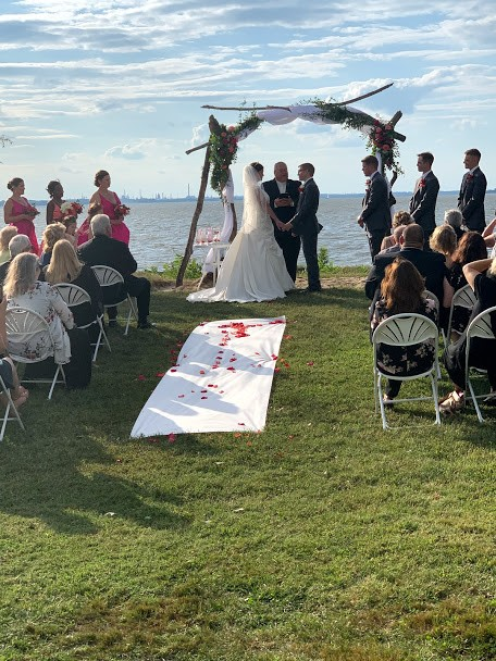 Rose petals on white cloth in aisle of outdoor wedding