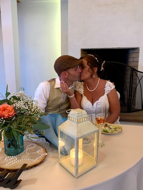 Bride and groom kissing at reception table