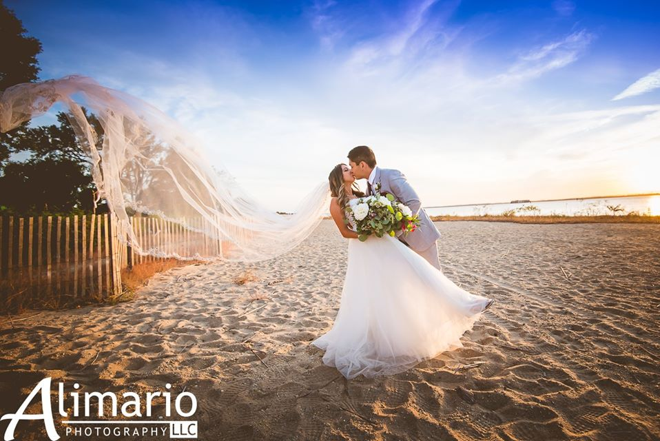 Bride and groom kissing on beach, veil blowing in wind