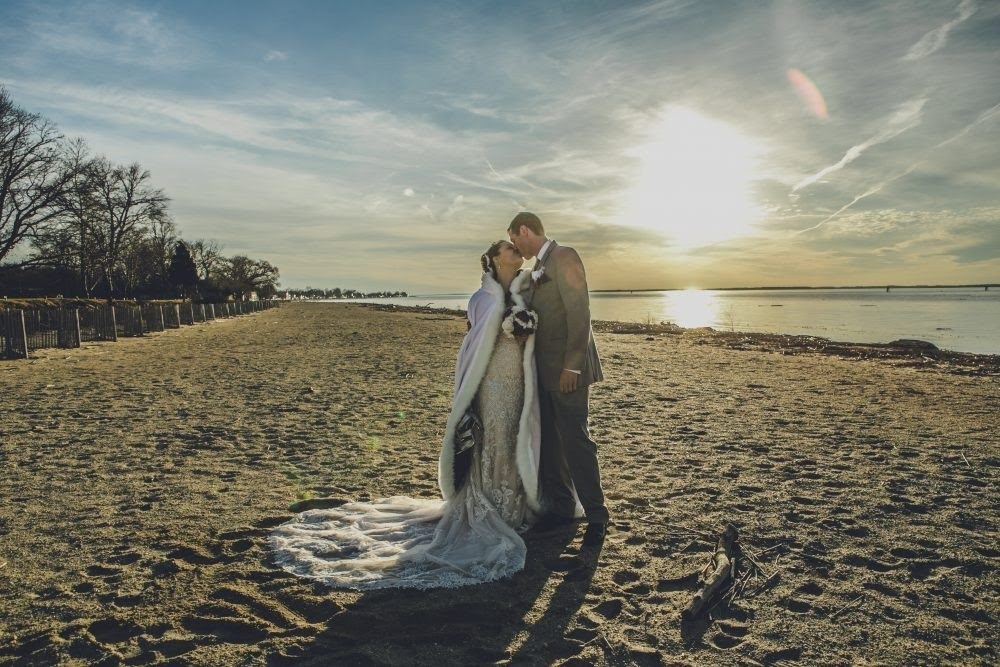 Bride and groom kissing on beach in front of sunset