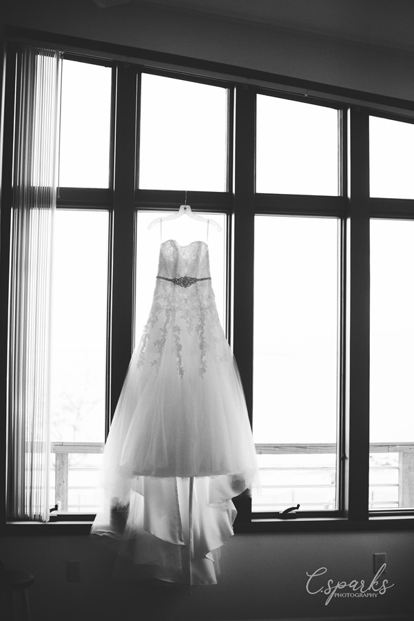 Black and white photo of bride's gown hung up