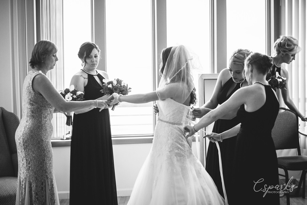 White and black photo of bride being dressed by bridesmaids