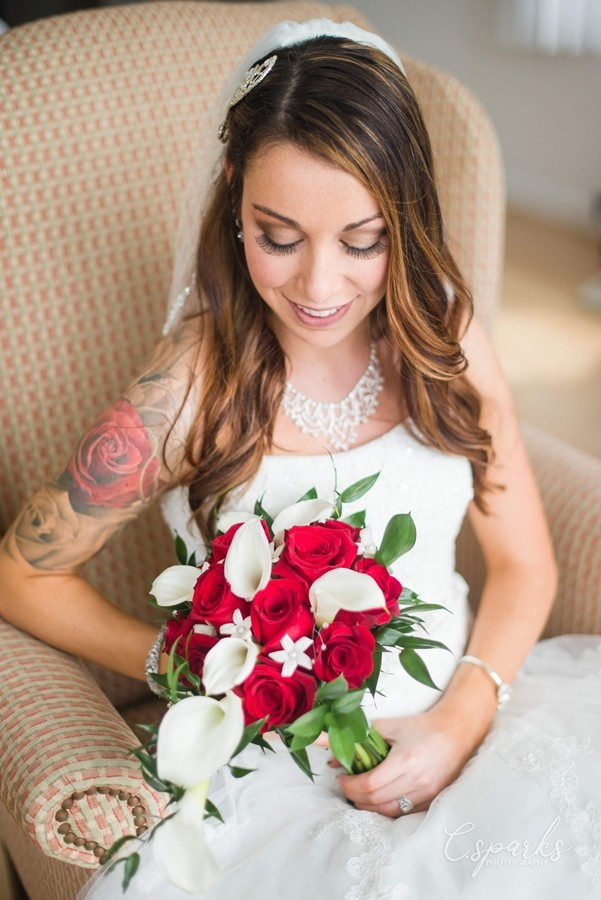 Bride sitting down holding red and white flowers