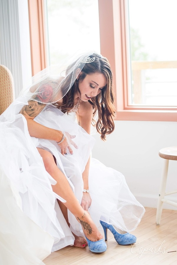 Bride in gown leaned over putting on her blue heels