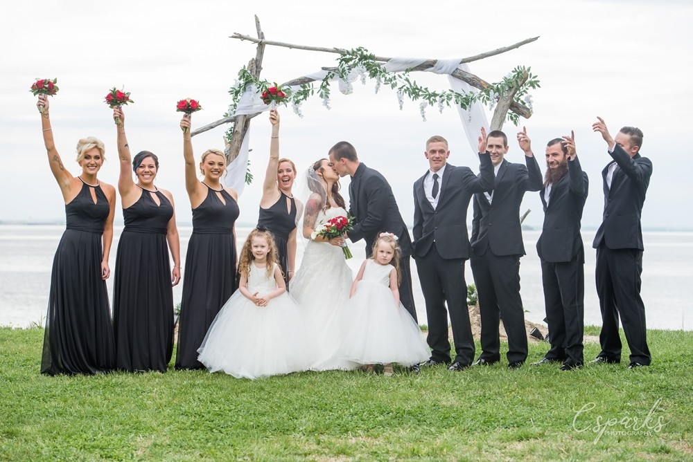 Bride and groom kissing in between maids and groomsmen with hands raised outside