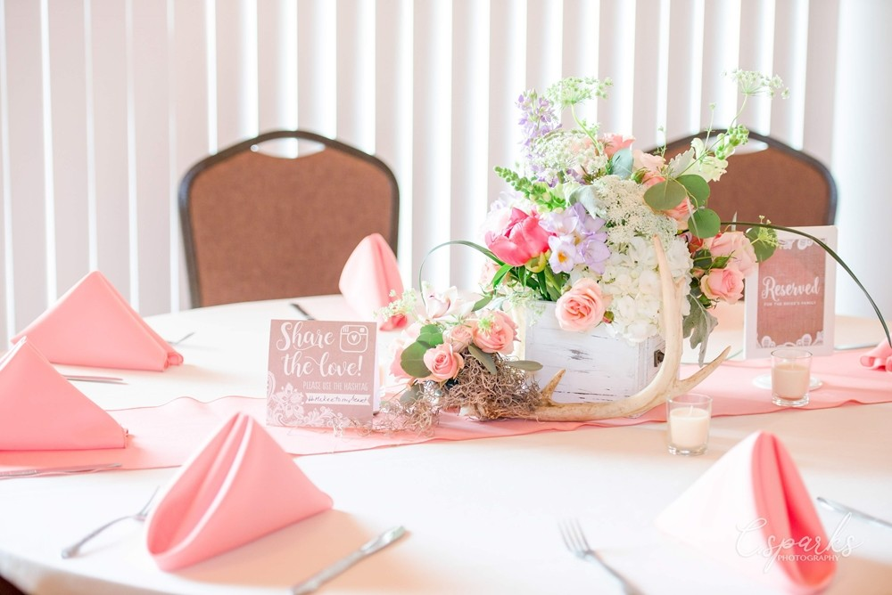 Round table set up with pink napkins and flowers at center