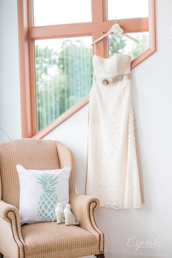 Bride's gown hanging up infront of window next to chair