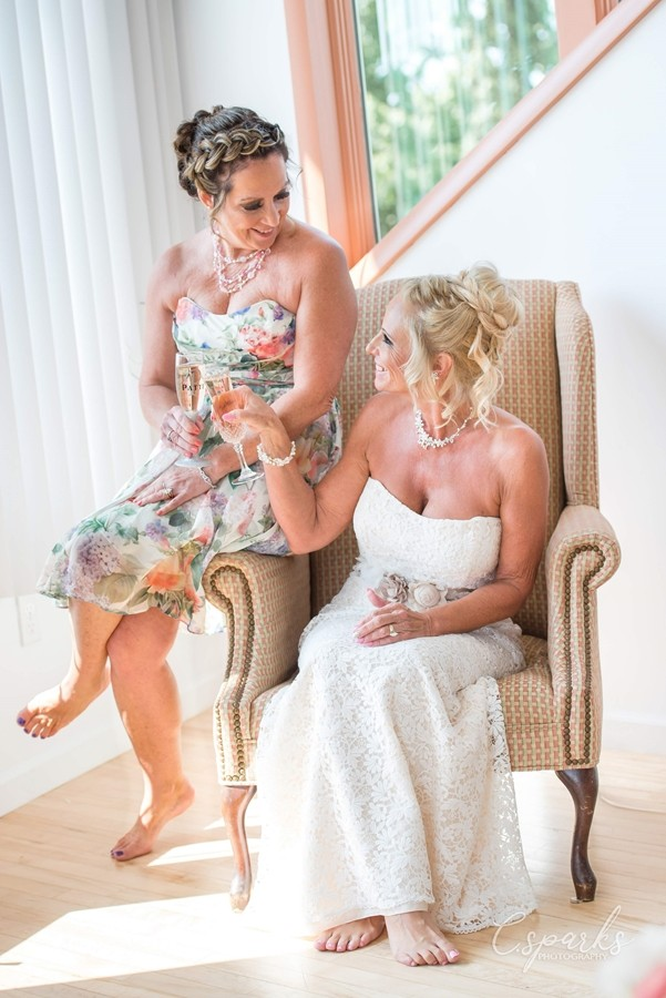 Bride sitting in chair holding glass up to bridesmaid