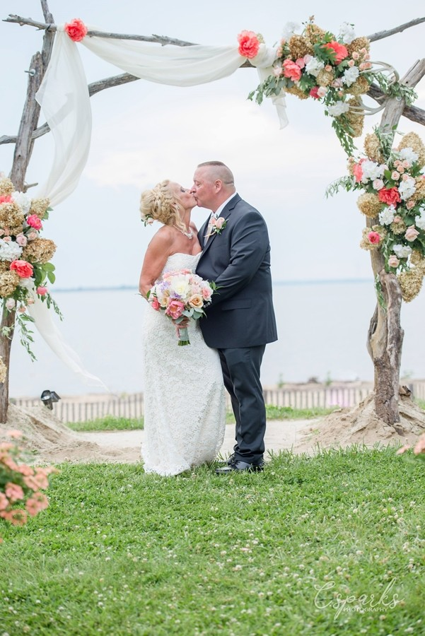 Bride and groom kissing under manor with blue skies