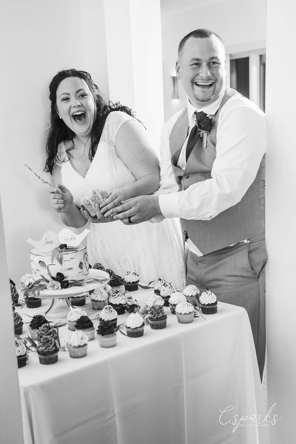 Black and white photo of bride and groom cutting the cake