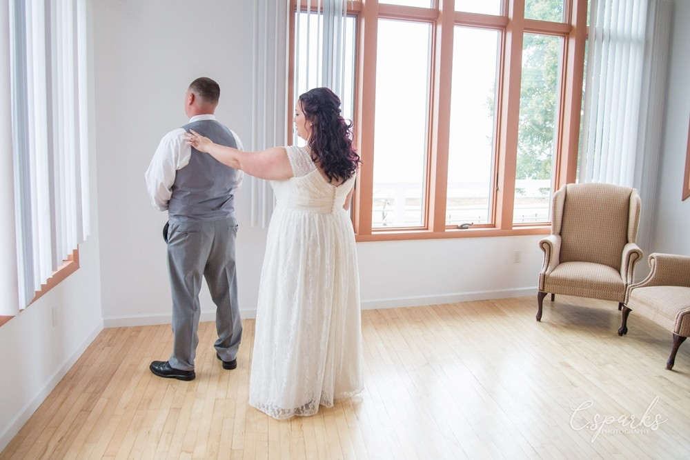 Bride with arm extended out and hand on groom's back