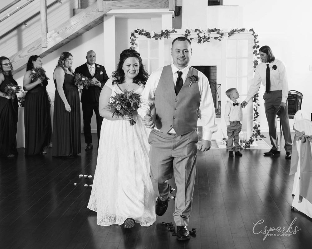 Black and white photo of bride and groom in center of ballroom