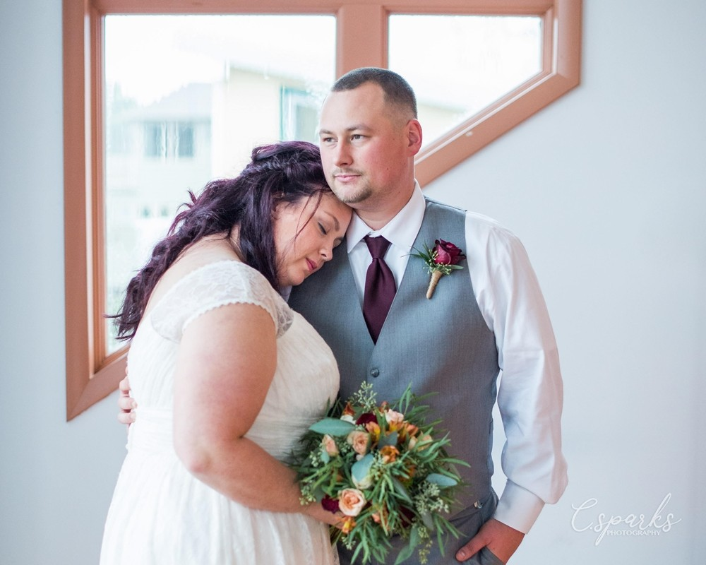 Bride leaning on groom's shoulder holding flowers