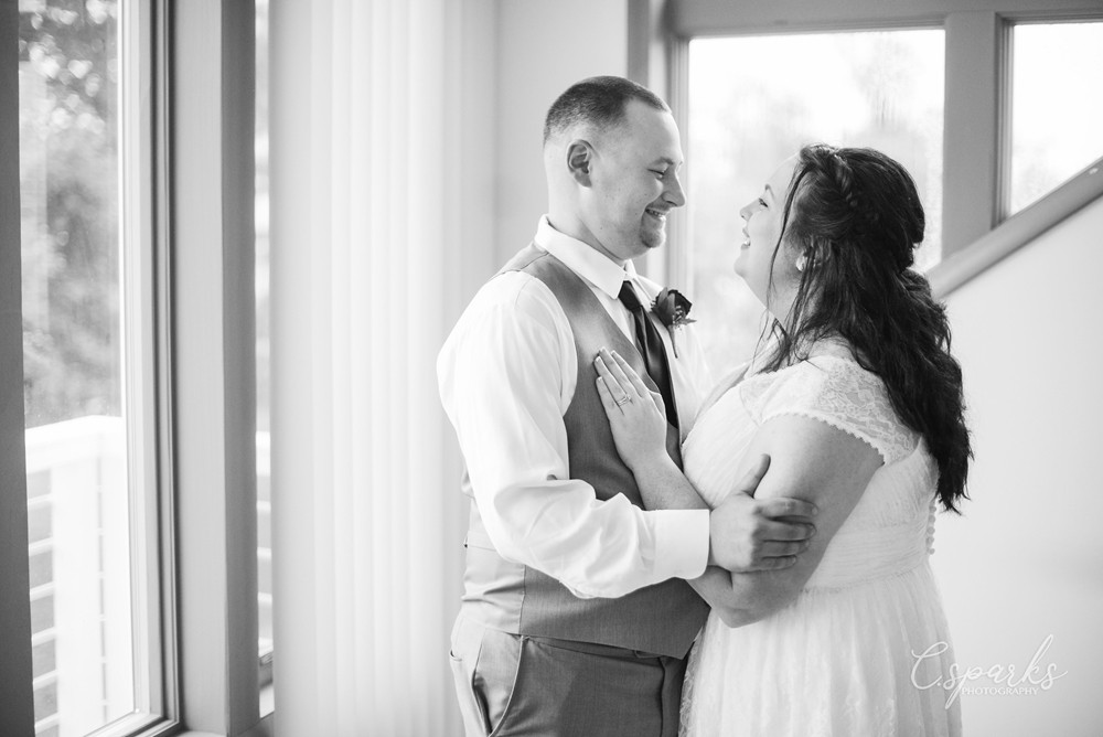 Black and white photo of bride and groom smiling at each other