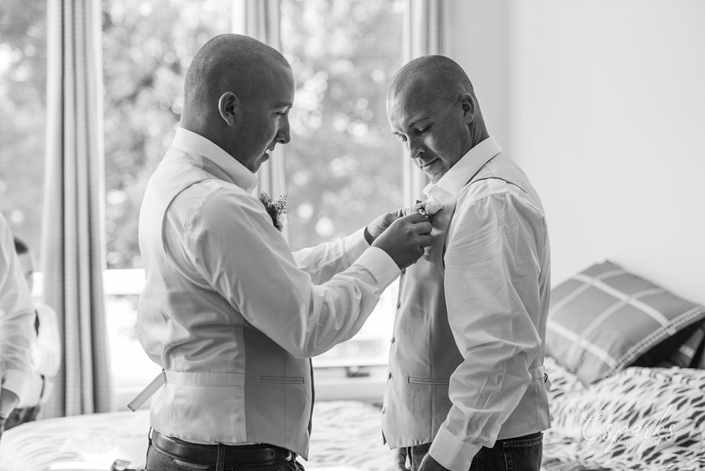 Groom and groomsman helping each other get ready for wedding