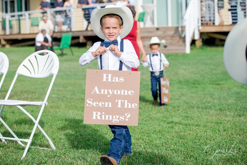 Ringbearer wearing sign that says Has Anyone Seen the Rings?