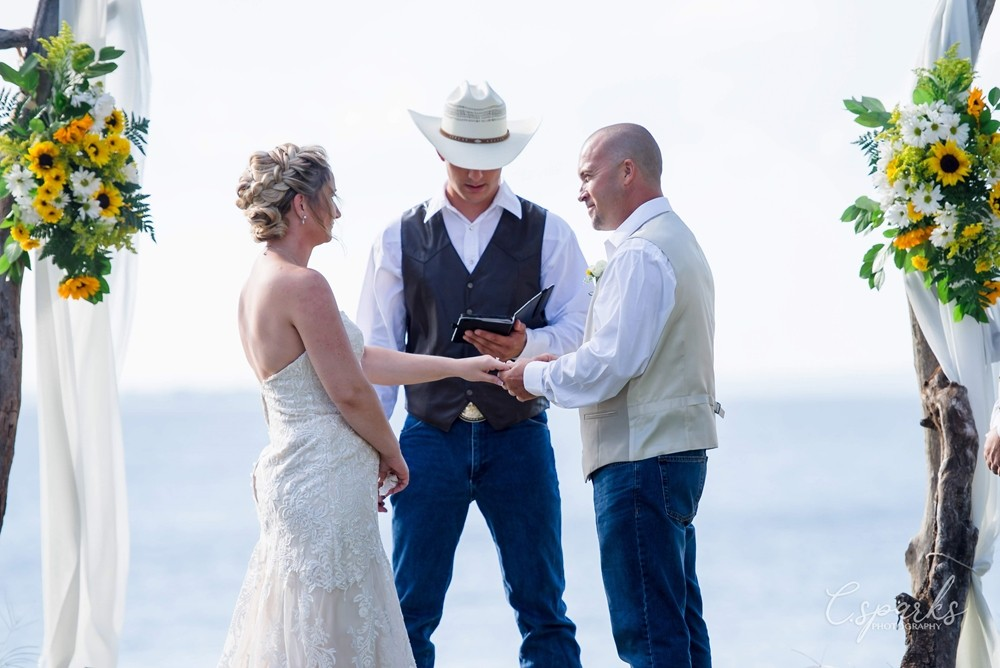 Bride and groom holding hands under manor, priest wearing cowboy hat