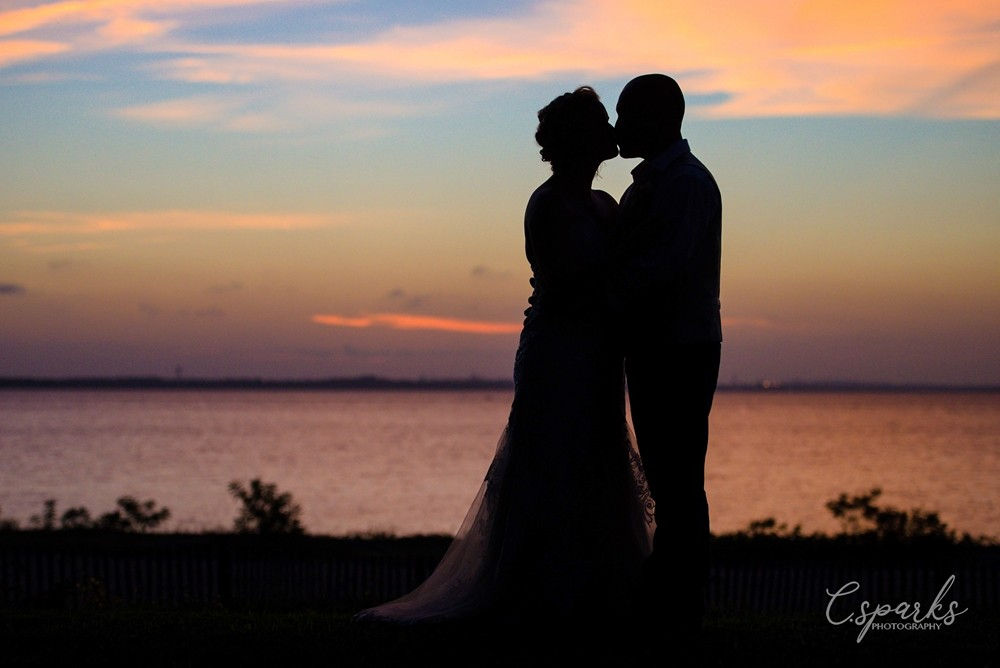 Dark silhouette of of bride and groom kissing infront os sunset and water