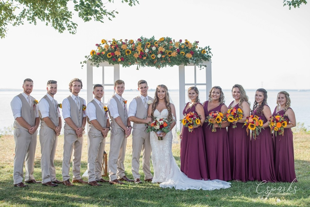 Gride and groom with bridesmaids and groomsmen posing infront of manor
