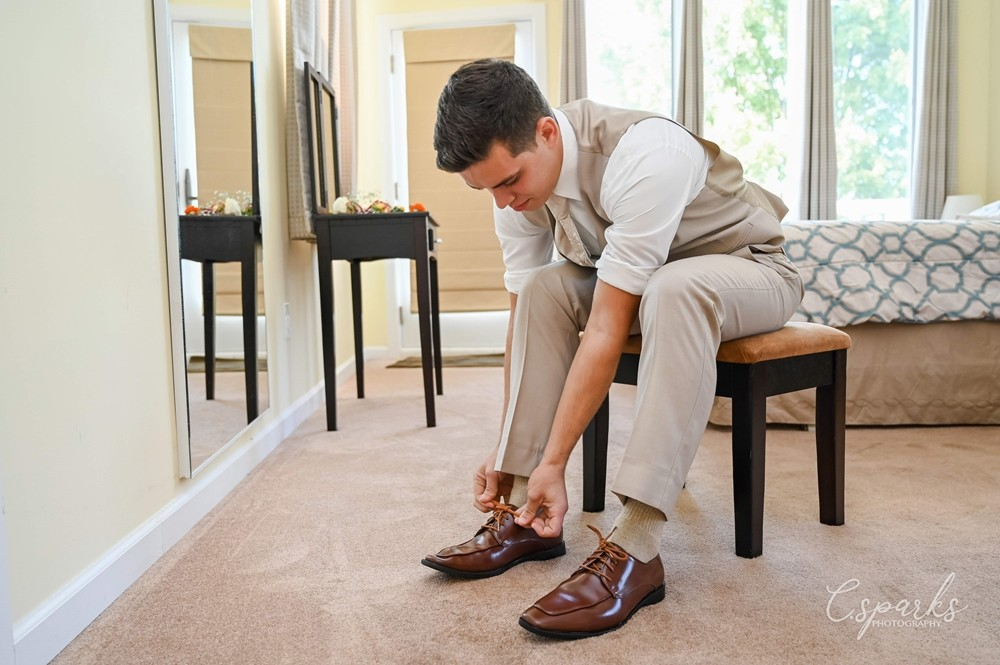 Groom putting on his shoes while sitting down