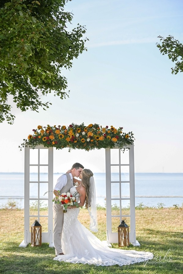 Bride and groom kissing on beach under manor
