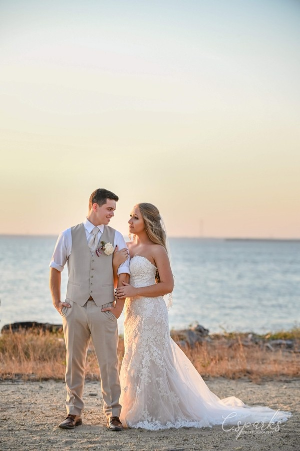 Bride and groom standing on beach infront of sunset