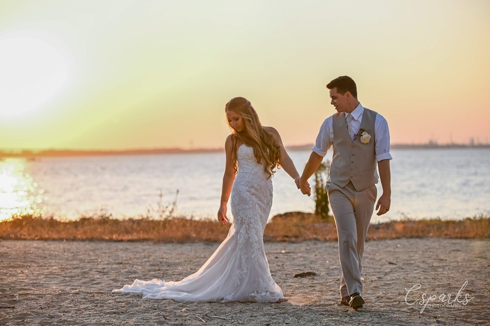 Bride and groom holding hands walking on beach during sunset