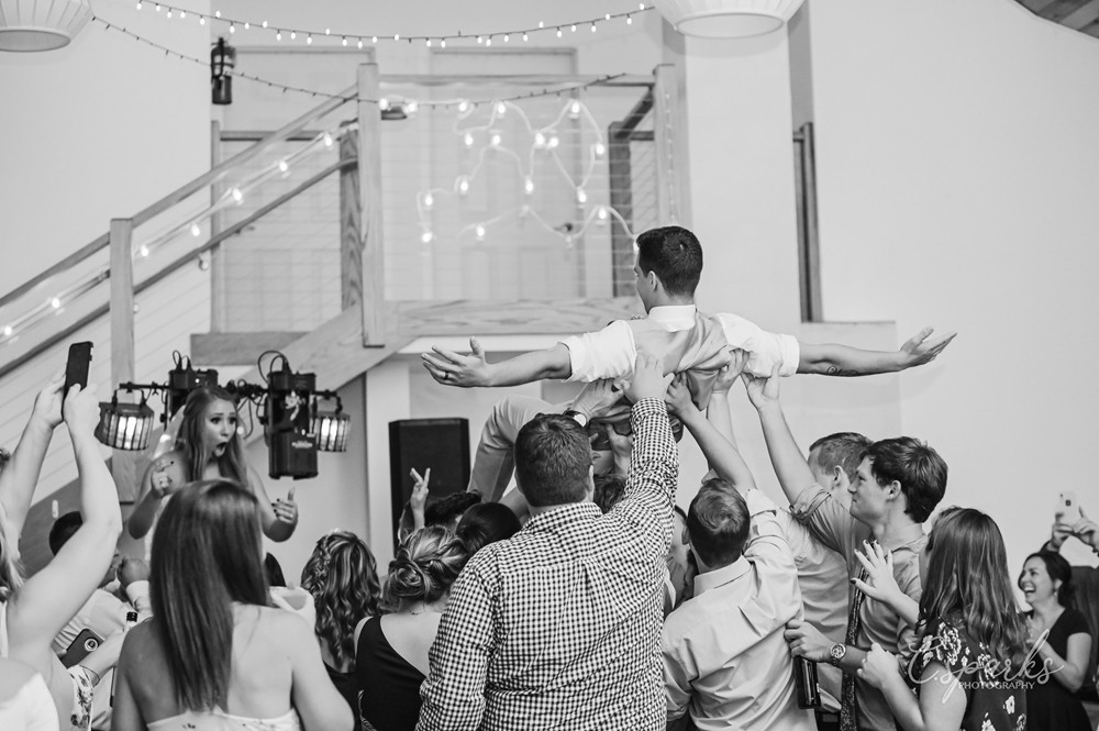 Black and white photo of groom crowd surfing over to bride