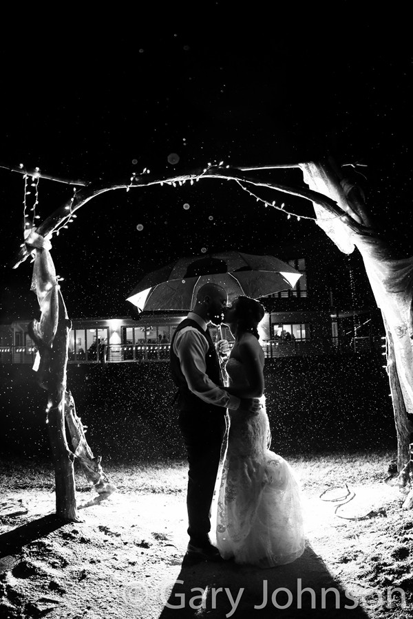 Black and white photo and bride and groom kissing under manor