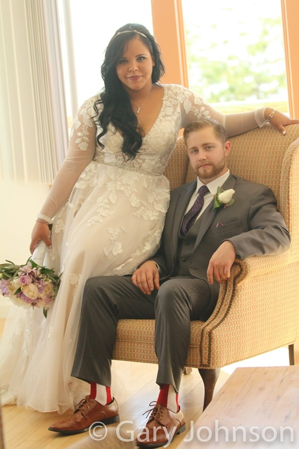 Groom sitting in char with bride leaning on side of chair