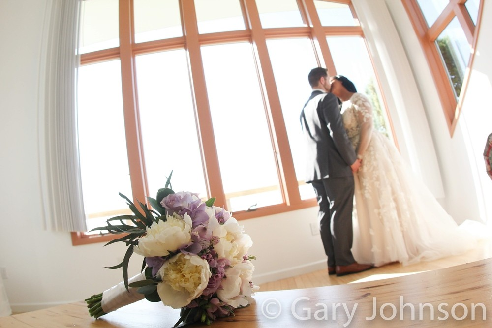 Flowers on table, bride and groom kissing in distance