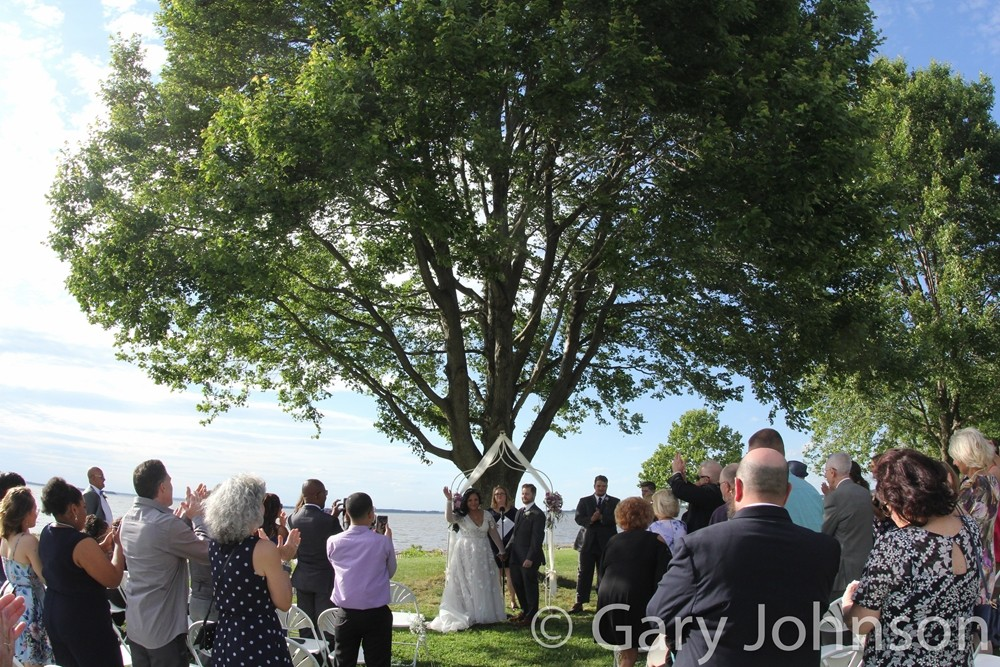 Outdoor wedding with bride and groom waving to families