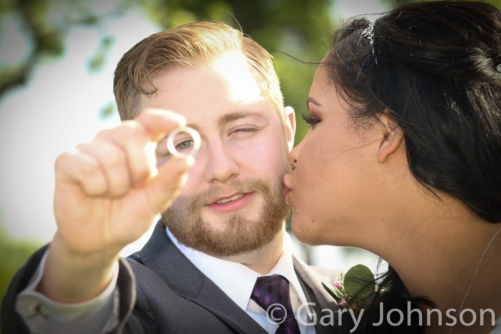 Bride kissing grooms cheek as he holds up ring to eye