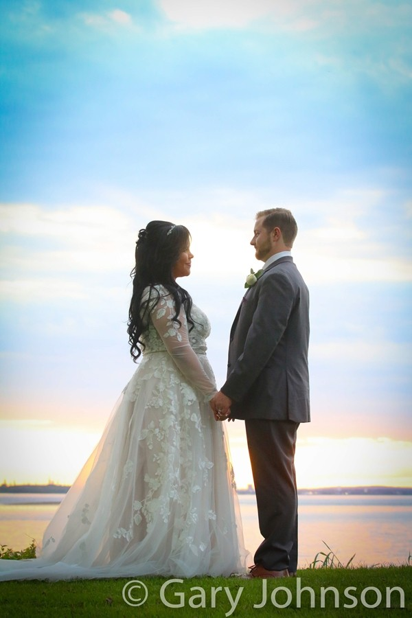 Bride and groom standing infront of sunset