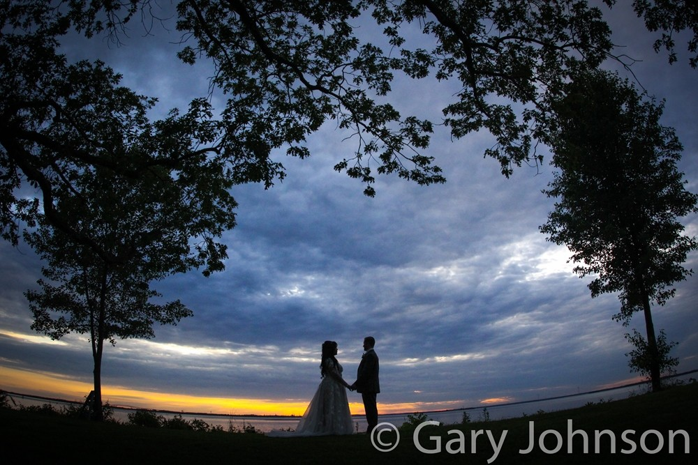 Bride and groom silhouettes with sunset and t