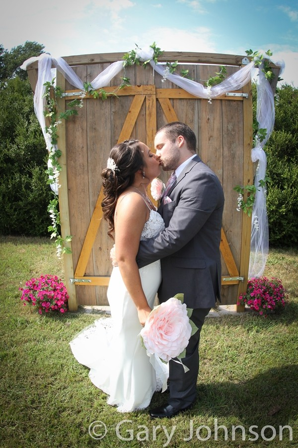 Bride and groom kissing in front of wooden backdrop in daylight
